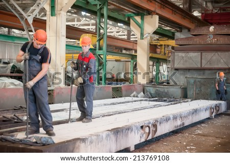 Tyumen, Russia - August 13, 2013: Block making department at construction material factory ZHBI-5. Workers in shop on production of steel concrete panels - stock photo
