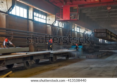 Tyumen, Russia - August 13, 2013: Finished goods warehouse at Concrete Goods Plant No. 5. Worker prepares railway platform for transportation of factory production - stock photo