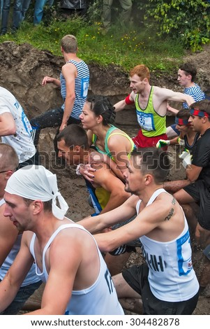 Tyumen, Russia - August 8, 2015: Steel Character command extrim race project on Krugloe lake and Gagarin park. Stage mud hole. Teams in action - stock photo