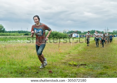 Tyumen, Russia - August 8, 2015: Steel Character extrim race on Krugloe lake. Gagarin park in Cape district. Running after obstacle stage - to get on inclined wall and to jump off in ditch with water - stock photo