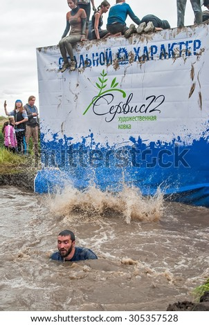 Tyumen, Russia - August 8, 2015: Steel Character extrim race on Krugloe lake. Gagarin park in Cape district. Obstacle stage - to get on inclined wall and to jump off in ditch with water - stock photo