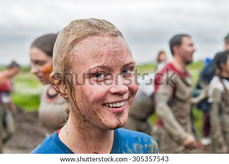 Tyumen, Russia - August 8, 2015: Steel Character extrim race on Krugloe lake. Gagarin park in Cape district. Obstacle stage. Happy dirty girl in action
