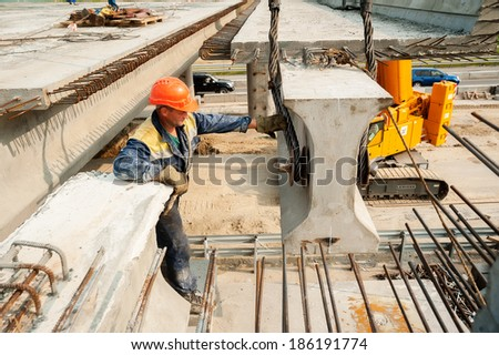Tyumen, Russia - July 31. 2013: JSC Mostostroy-11. Bridge construction for outcome of the Tobolsk path and Bypass road round Tyumen. Workers mount bridge span - stock photo