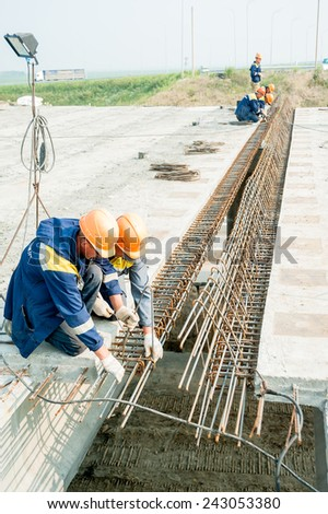 Tyumen, Russia - July 31, 2013: JSC Mostostroy-11. Bridge construction for outcome of the Tobolsk path and Bypass road round Tyumen. Workers make fittings bindingon on bridge construction - stock photo