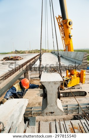 Tyumen, Russia - July 31, 2013: JSC Mostostroy-11. Bridge construction for outcome of the Tobolsk path and Bypass road round Tyumen. Workers mount bridge span - stock photo