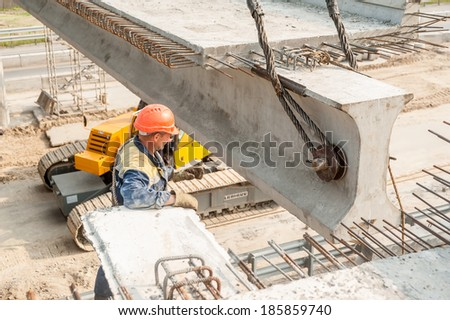 Tyumen, Russia - July 31. 2013: JSC Mostostroy-11. Bridge construction through Tyumen-Tobolsk path. Workers mount bridge span - stock photo
