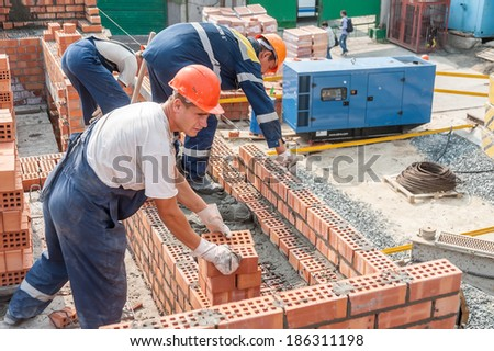 Tyumen, Russia - July 31, 2013: JSC Mostostroy-11. Construction of a 18-storeyed brick residental house at the intersection of streets of Nemtsov and Tsiolkovsky. Team of bricklayers behind work - stock photo