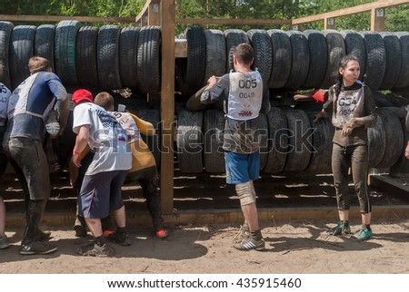 Tyumen, Russia - June 11, 2016: Race of Heroes project on the ground of the highest military and engineering school. Sportsmen move between old tires. Human birth stage