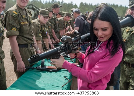 Tyumen, Russia - June 11, 2016: Race of Heroes project on the ground of the highest military and engineering school. Exhibition of weapon. Girl considers anti-tank rocket propelled grenade launcher - stock photo