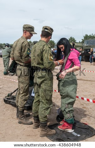 Tyumen, Russia - June 11, 2016: Race of Heroes project on the ground of the highest military and engineering school. Exhibition of weapons. Girl - visitor of show puts on sapper suit