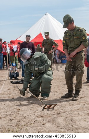 Tyumen, Russia - June 11, 2016: Race of Heroes project on the ground of the highest military and engineering school. Exhibition of weapon. Visitors of show try on the sapper suit