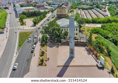 Tyumen, Russia - June 27, 2015: Stella with eternal flame and building of City Council museum on place of foundation of city. Merge of streets of the Republic and Lenin