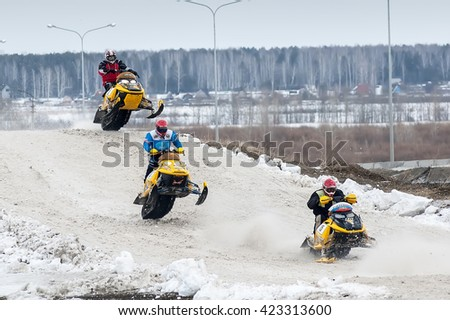 Tyumen, Russia - March 08. 2008: IV stage of personal-team Championship of Ural Federal district in over-snow cross-country. Jump of three sportsmen on snowmobile