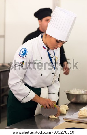 Tyumen, Russia - March 23. 2016: Open championship of professional skill among youth. Worlld skills Russia Tyumen - 2016. Girl-cook prepares food in competition of masters of cook business - stock photo