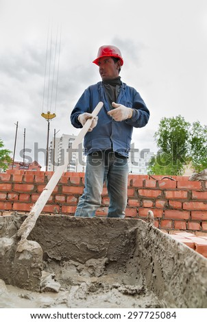 Tyumen, Russia - May 23, 2008: Construction of 18 floor brick residental house at intersection of streets of Gercena and Chelyuskincev. Builder man working with shovel during concrete cement solution - stock photo