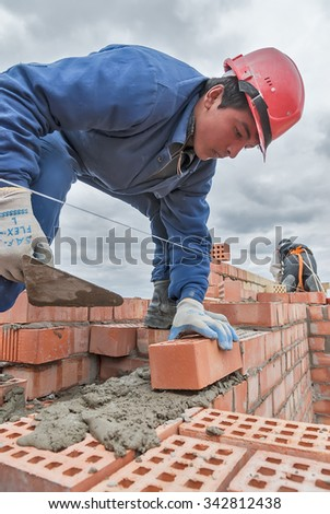 Tyumen, Russia - May 23, 2008: Construction of 18 floor brick residental house at intersection of streets of Gercena and Chelyuskincev. Bricklayer behind work on 15th floor of the building - stock photo