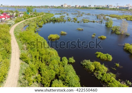 Tyumen, Russia - May 16, 2016: Naberezhnaya Street is protected by a dam from the spread river. On background on other river bank there is the First Zarechny residential district - stock photo
