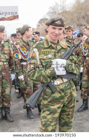 Tyumen, Russia - May 9. 2009: Parade of Victory Day in Tyumen. Attractive girl in military uniform against pupils from patriotic clubs. There is preparation for parade - stock photo