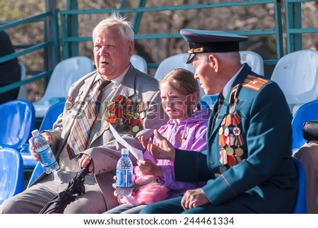 Tyumen, Russia - May 9. 2009: Victory Day in Tyumen. Senior veterans of World War II with great-granddaughter on tribune - stock photo