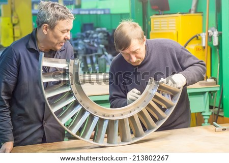 Tyumen, Russia - November 14, 2007: JSC Tyumenskie Motorostroiteli (Plant on production and repair of aviation engines). Mechanics assembles parts for aviation engine