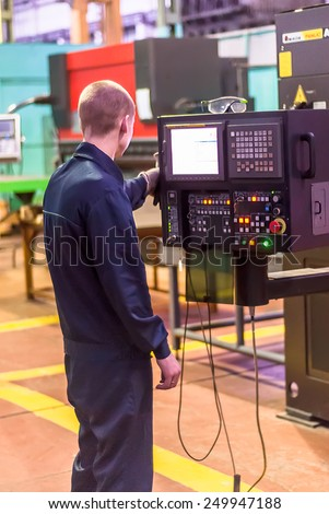 Tyumen, Russia - November 14, 2007: JSC Tyumenskie Motorostroiteli (Plant on production and repair of aviation engines). Technician operates computerized metalworking machine - stock photo