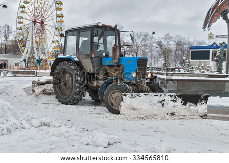 Tyumen, Russia - November 29, 2008: Tractor with snowplowing equipment cleans street in snowstorm weather - stock photo