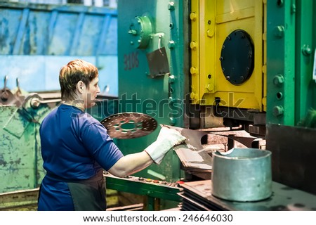 Tyumen, Russia - September 7, 2010: JSC Tyumenskie Motorostroiteli (Plant on production and repair of aviation engines). Woman stamps details on hydraulic press - stock photo