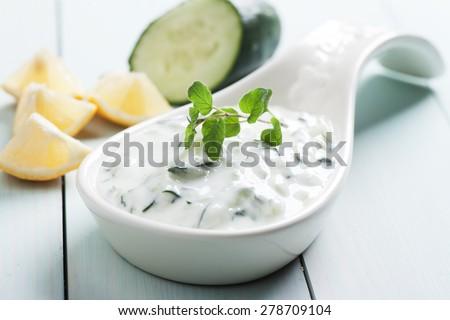 Tzatziki or cacik, cucumber and yogurt salad with mint leaves - stock photo