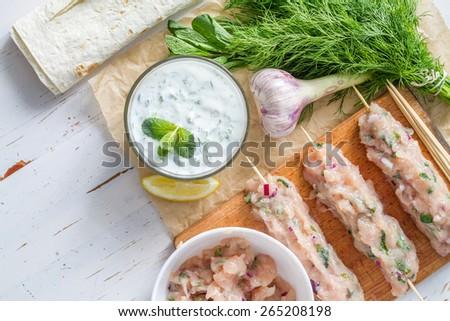 Tzatziki sauce in glass bowl, souvlaki, meat, mint, onion, lemon, skewer, white wood background, top view - stock photo