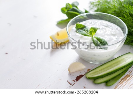 Tzatziki sauce in glass bowl, with ingredients - cut cucumber, mint, dill, lemon, garlic, white wood background - stock photo