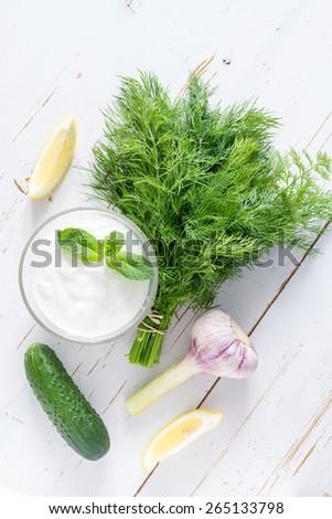Tzatziki sauce ingredients - yogurt, cucumber, lemon, mint, dill on white wood background, top view - stock photo