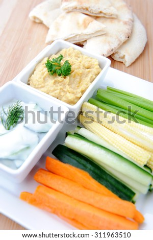 Tzatziki (yoghurt and cucumber) and hummus (chickpea) dips with raw carrot, cucumber, corn and celery with pita or naan bread  - stock photo