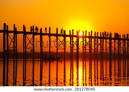 U Bein Bridge at sunset with people crossing Ayeyarwady River, Mandalay, Myanmar - stock photo