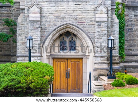 U of T or University of Toronto: Trinity College. Beautiful vintage wooden door with flowers at its side. The landmark features Jacobethan Tudor architecture