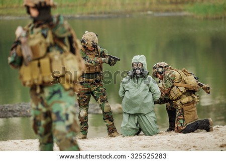 U.S. Army rangers captured a scientist with protective mask and protective clothes  during the military operation