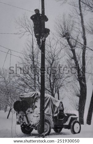 U.S. Army Signal Corp lineman repairing damaged phone lines in France. Winter of 1944-45, World War 2. B&W Photo with oil color. - stock photo