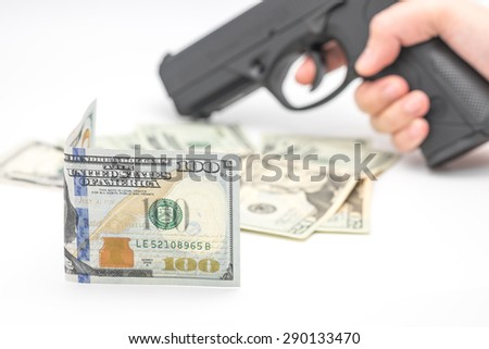 U.S. dollar banknotes with hand holding pistol for robbery background   - stock photo