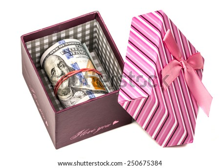 U.S. dollars banknotes laying in pink bow decorated gift box. - stock photo