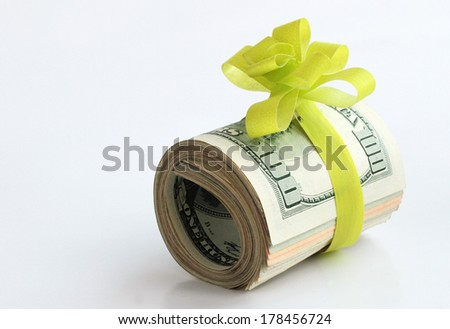 U.S. dollars banknotes with a green ribbon as a gift of money  - stock photo