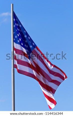 U.S. flag on a background of blue sky - stock photo