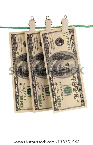 U.S. hundred dollar banknotes fixed pegs on a green rope. - stock photo