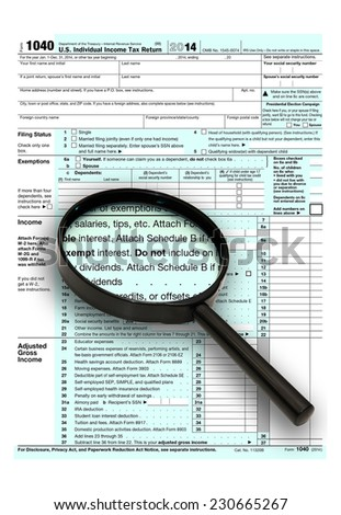 U.S. Individual Income Tax Return for 2014 with a magnifying glass. Isolated on a white background.