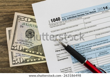 U.S. individual income tax return form 1040 with pen and money - stock photo