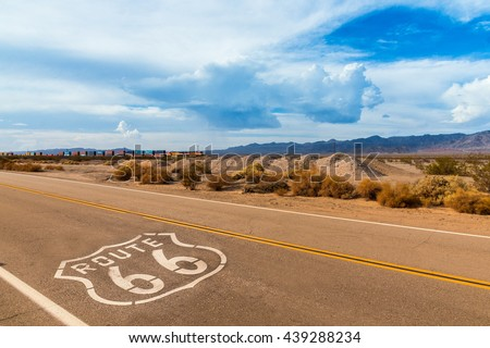 U.S. Route 66 highway, with sign on asphalt and a long train in the background, near amboy, california. Located in the mojave dessert - stock photo