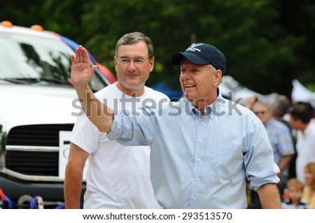 U.S. Senator Lindsey Graham, Republican of South Carolina, waves at the crowd during the July 4 parade in Amherst, New Hampshire, on July 4, 2015. Campaign aide Paul Young is in the background.  - stock photo