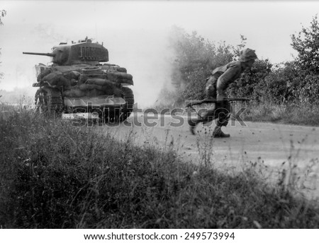 U.S. soldier crosses a road cautiously under the cover of light tank in the Hedgerows of Normandy. The tank is equipped with the hedgecutter device developed in July 1944. Normandy Campaign, France. - stock photo