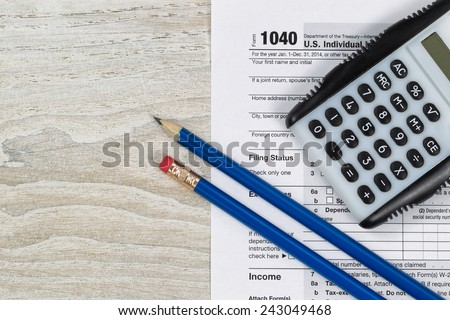 U.S. Tax form 1040 with calculator and pencils on wooden desktop  - stock photo