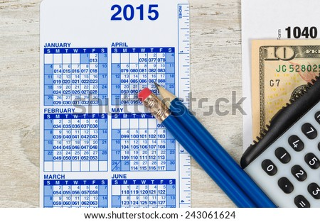 U.S. Tax form 1040 with calculator, calendar, currency and pencils on wooden desktop   - stock photo