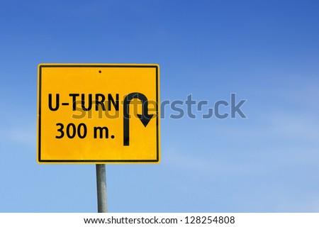 U turn road sign on sky background - stock photo