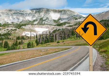 U-Turn Sign:  A sign warns motorists of a sharp bend ahead on a mountain road in southern Wyoming.  - stock photo